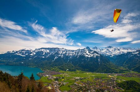 Paraglider flying over mountains and Interlaken valley against picturesque sky at sunny summer day, Interlaken, Swiss Alps