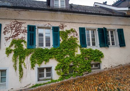 House wall covered in ivy with windows with open shutters on cobbled street descending on hillside, Solothurn, Switzerland Stok Fotoğraf