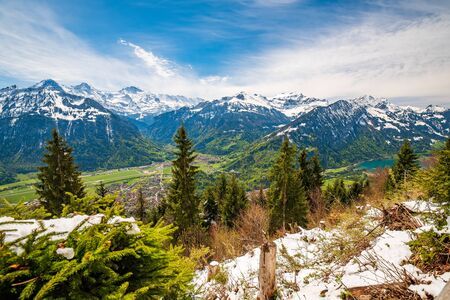 Fresh snow on mount slope on Harder Kulm - popular viewpoint over Interlaken, Swiss Alps, Switzerland. Famous Jungfrau peak and Alpine ridges under picturesque sky on background