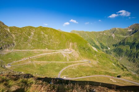 Scenic view of the winding Transfagaras mountain road in the Transylvanian Alps, Carpathian Mountains, Romania. Mountain road with serpentine with a beautiful view of the pass in sunny day. 스톡 콘텐츠
