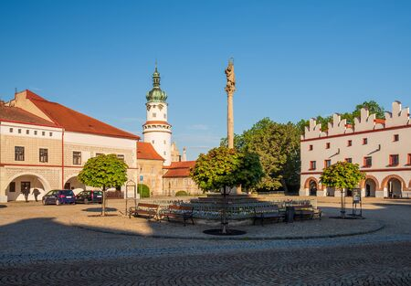 Morning view of column with statue of Virgin Mary renaissance building and castle tower on Husovo square, Nove Mesto nad Metuji, Czech Republic