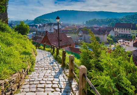 Stone paved alley on hillside of medieval fortified city of Sighisoara, Transylvania region, Romania. Birthplace of Vlad Dracula. Stock Photo