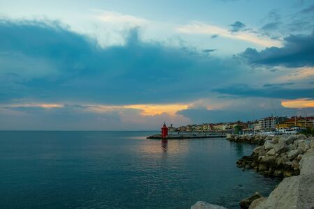 Picturesque view of coastline of Adriatic sea with colorful houses and lighthouse in sunset light at summer evening in Piran, Slovenia. Travel destination scene