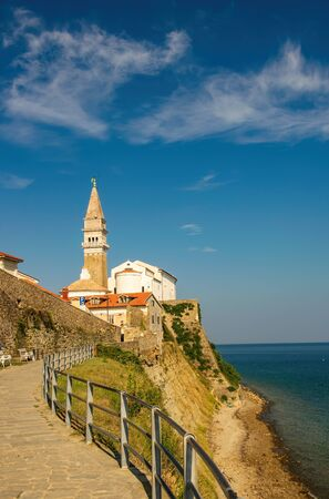 Picturesque view of coastline of Adriatic sea with alley along Piran old city walls and Cathedral of Saint George on background, Slovenia