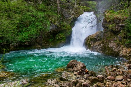 Picturesque Sum waterfall at spring flood on Radovna river in the end of Vintgar gorge, Slovenia. Vintgar Gorge is a popular tourist attraction near famous Bled Lake