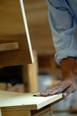 A worker sanding a wooden chair with sandpaper