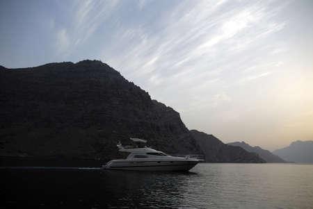 musandam: Yacht Cruising In Mountainous Landscape At Sunset