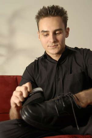 A Young Man Polishing A Shoe