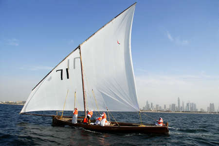 Sailing Dhow Against The Distant Cityscape Of Dubai