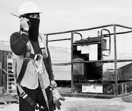 Construction Worker Wearing Protective Gear & Using A Handheld Transceiver photo