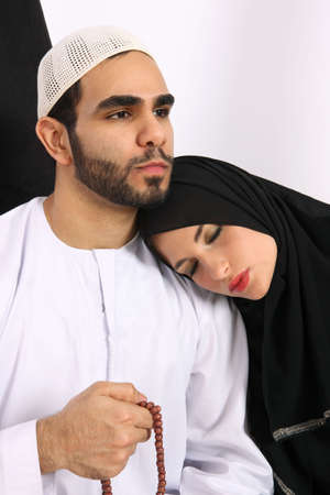 Arabic Husband Counting Prayer Beads While His Wife Is Asleep On His Shoulder