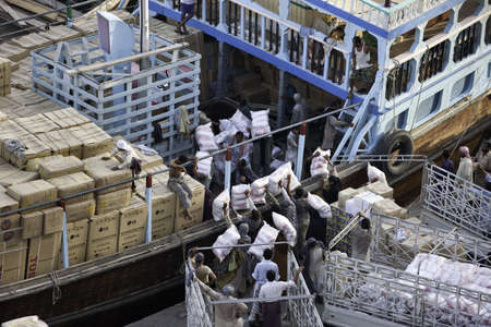 Workers Loading A Small Ship In Deira Port In Dubai Stock Photo