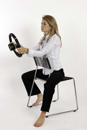 Girl Sitting On A Chair & Holding A Steering Wheel In Her Hands Stock Photo
