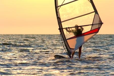 Windsurfing on orange sunset's background Reklamní fotografie
