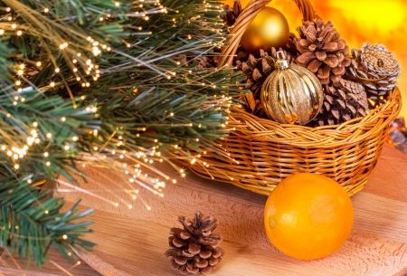 Basket with pine cones and Christmas balls under the tree near a fireplace photo