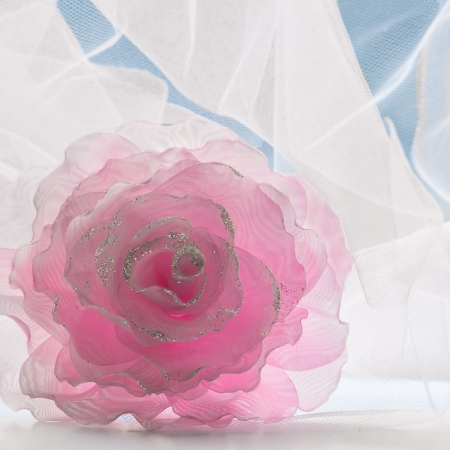Pink decoration flower against white openwork fabric and blue sky