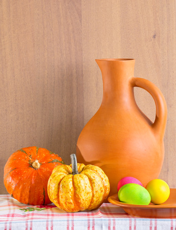Still life with jug,  pumpkins and Easter eggs at the checkered tablecloths photo
