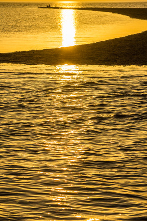 Gold sunset over the sand spit in the sea  in the summer evening photo