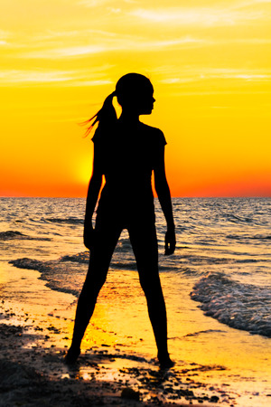 gleam: Silhouette of a girl on the beach on a background picturesque sunset Stock Photo