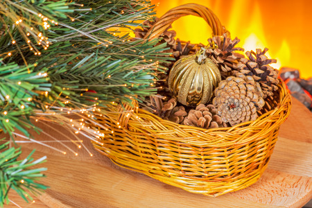 Basket with pine cones and New Year ball under the fir near a fireplace photo