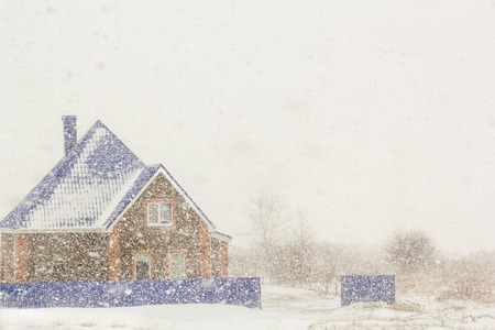 plentiful: House on the background of plentiful snowfall on a winter day Stock Photo