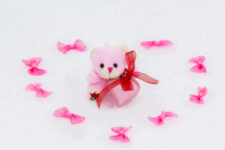 pink teddy bear: Heart of pink ornamental bows and pink teddy bear with pink heart on white snow on Valentines Day