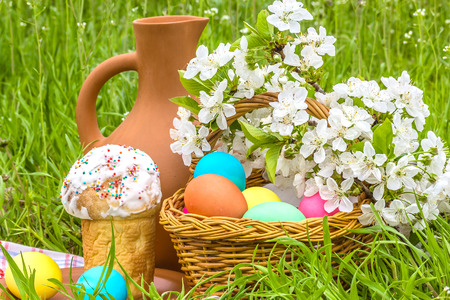 painted eggs: Wicker basket with painted eggs, Easter cakes, a clay jug and flowering branch cherry in the spring garden
