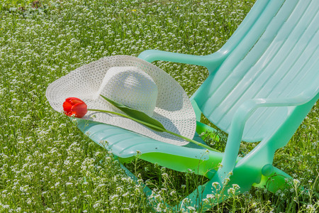 Deckchair, tulip and hat in the spring garden against the backdrop of cherry blossoms photo