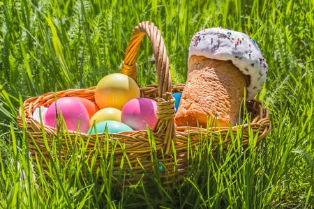 painted eggs: Wicker basket with painted eggs and Easter cake on the spring green grass