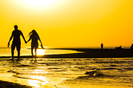 Golden sunset over the sea and the silhouettes of the lovers in the summer evening photo