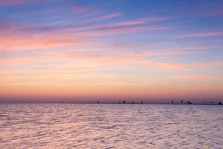 夏の夜の背景の美しい紫夕日に青い海と人々 のシルエットの砂嘴