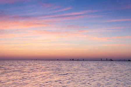 sandbank: Sand spit in the blue sea and people silhouettes on a background picturesque purple sunset in the summer evening