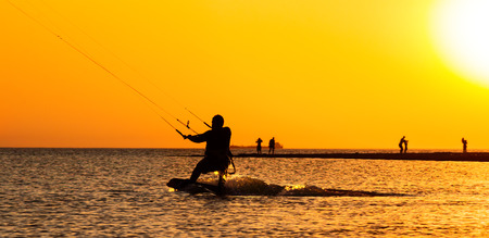 kite surfing: Kite surfing on the background of orange sunset in the sea Stock Photo