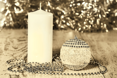 lustre: Christmas ball, candle and beads on wooden boards in soft background of tinsel, sepia. Selective focus