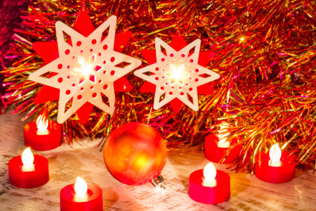 starlet: Christmas composition with ball, stars and candles close up on a festive background of tinsel. Selective focus