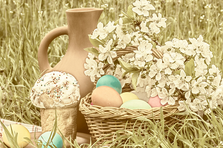 flowered: Wicker basket with painted eggs, Easter cakes, a clay jug and flowering branch cherry in the spring garden. Photo toned Stock Photo