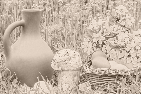 painted eggs: Wicker basket with painted eggs, Easter cakes, a clay jug and flowering branch cherry in the spring garden, sepia