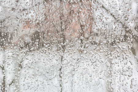winter thaw: Texture of the ice and drops on the window glass in a bad winter day Stock Photo