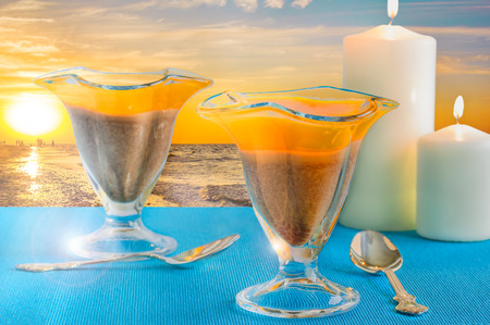 gold table cloth: Two glasses with orange-chocolate jelly and candles on the background of beautiful sunset on the beach Stock Photo