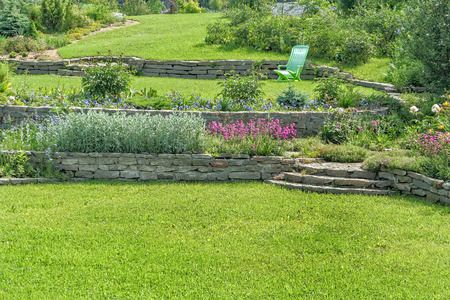 Beautiful blooming garden with retaining walls, lawns and flower gardens on a sunny summer day