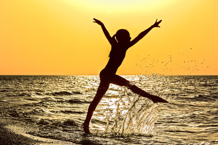 girlie: Silhouette of a girl running in the sea  in a spray of water at orange sunset