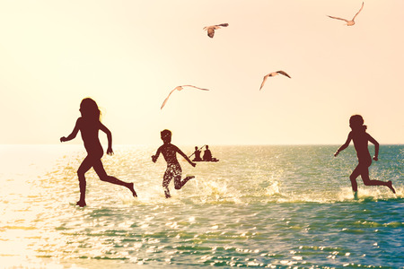 iluminado a contraluz: Siluetas de los niños que se ejecutan a través del agua en el mar al atardecer, con retroiluminación Foto de archivo