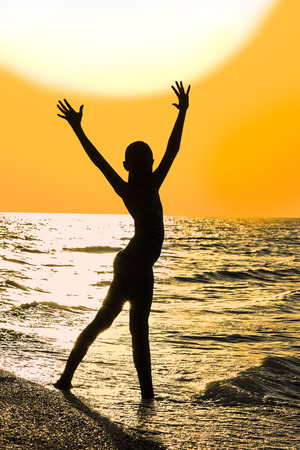 raised hands: Silhouette of girl with raised hands on the beach on the background of gold sunset Stock Photo