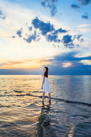sundress: Girl in a white sundress standing in the sea on a background picturesque sunset on a summer evening Stock Photo