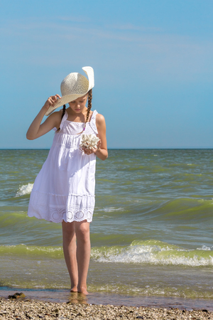 summer holidays: Girl in a white sundress and white hat examines coral on the beach
