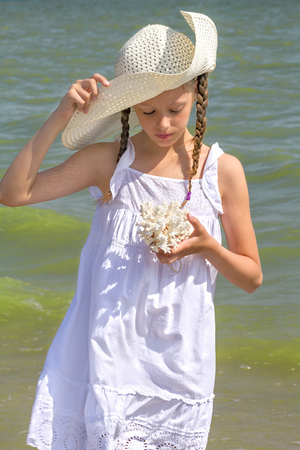 sundress: Girl in a white sundress and white hat examines coral on the beach, close up Stock Photo