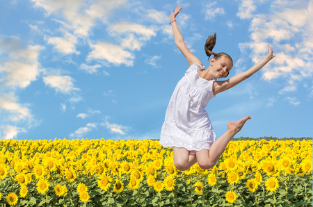 Cheerful girl in white sun-dress jumping on a background of a field of yellow sunflowers and blue sky