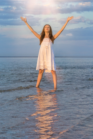 Girl in a white sundress standing in the water at the beach with their hands raised in the last rays of the sun and says goodbye to the setting sun
