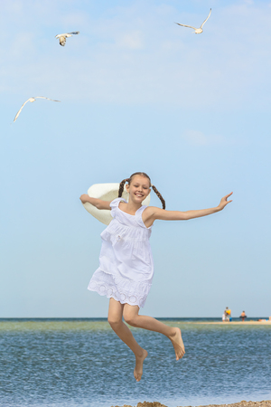 Joyful girl in a white sundress and a white hat in his hand  jumping over the water on the beach against the sea and a blue sky on a sunny summer day
