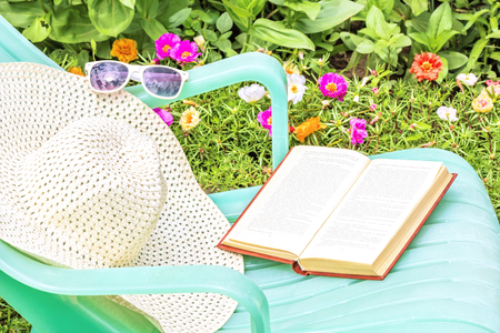 day flowering: Relax with a book in the garden on a sunny summer day. Green chaise lounge, a white hat and sunglasses on a background of flowering flowerbed